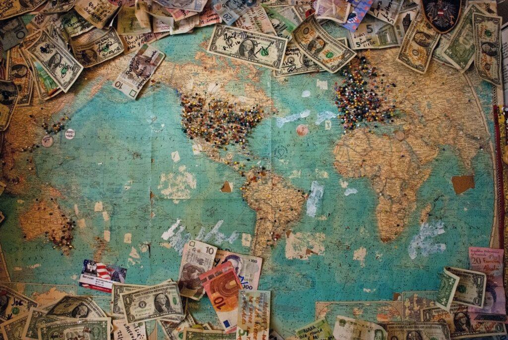 世界地図の上にお金が散らばってる